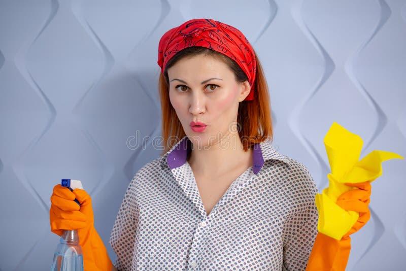 Портрет женщины с поставками чистки на голубой предпосылке стоковые изображения