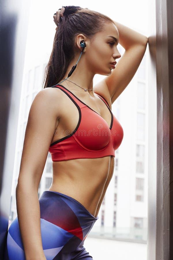 Портрет женщины фитнеса sporty в наушниках во время на открытом воздухе разминки тренировок Красивая девушка пригонки Модель фитн стоковые изображения rf