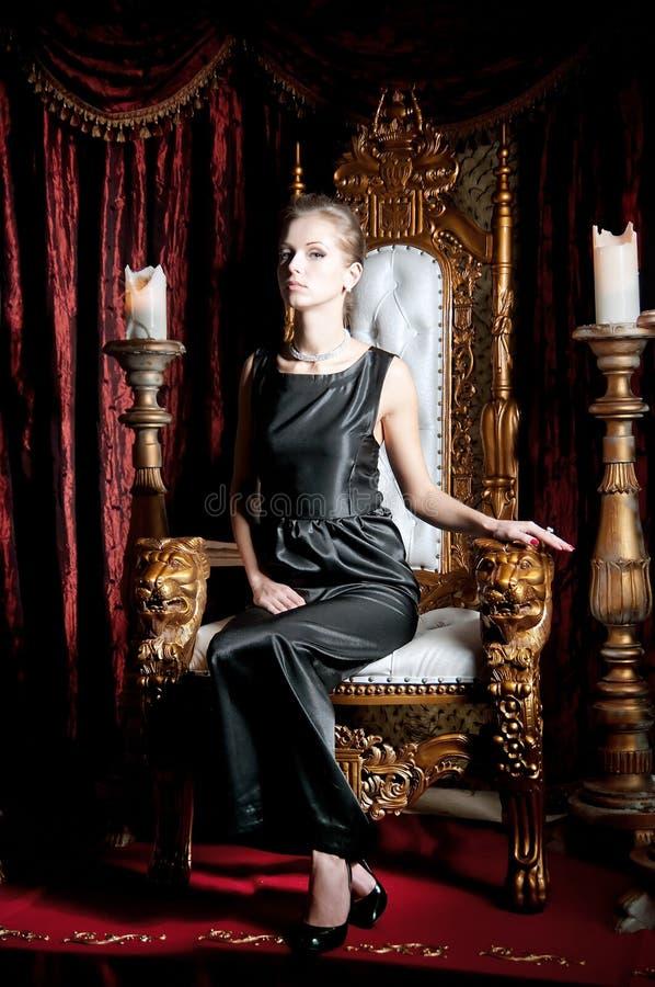 Портрет женщины элегантности привлекательной сидя на троне стоковое изображение rf
