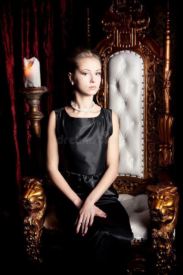 Портрет женщины элегантности привлекательной сидя на троне стоковые фотографии rf