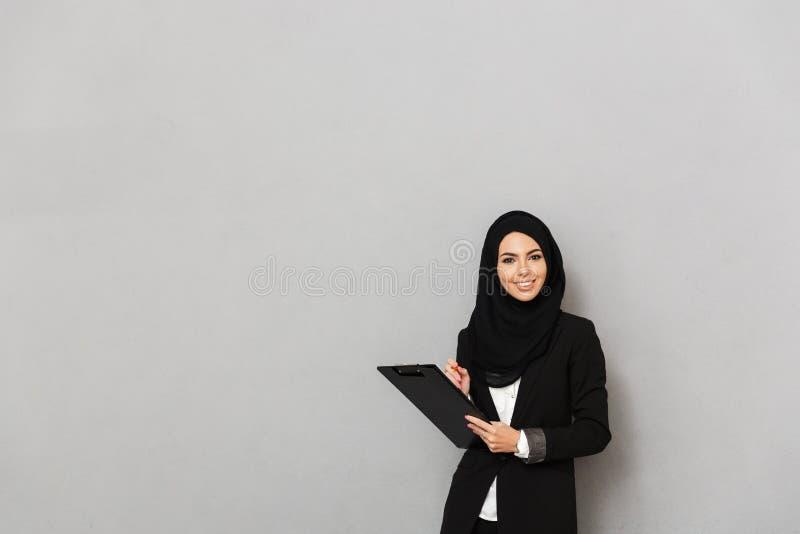 Портрет женщины 20s мусульман усмехаясь в черном традиционном clothi стоковое фото rf