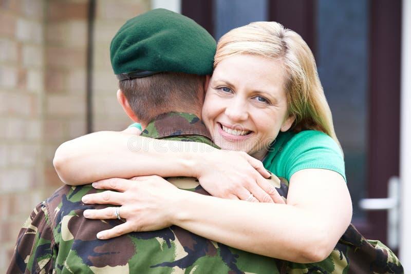 Портрет жены обнимая дом супруга армии на разрешении стоковые фотографии rf