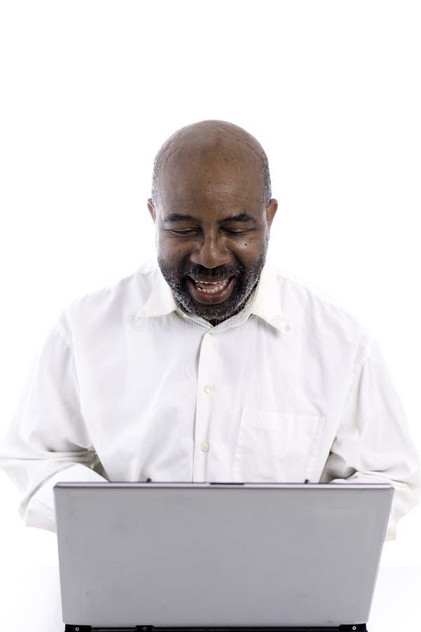 Портрет жизнерадостного Афро-американского специалиста программного обеспечения смеясь пока сидящ фронт ноутбука стоковые изображения rf