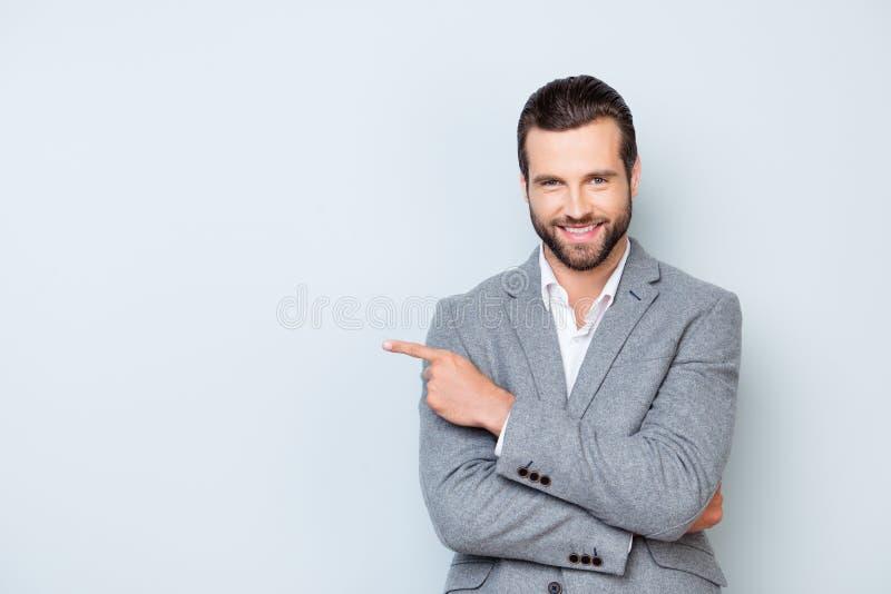 Портрет жизнерадостного радостного человека в официально костюме стоя против g стоковое изображение