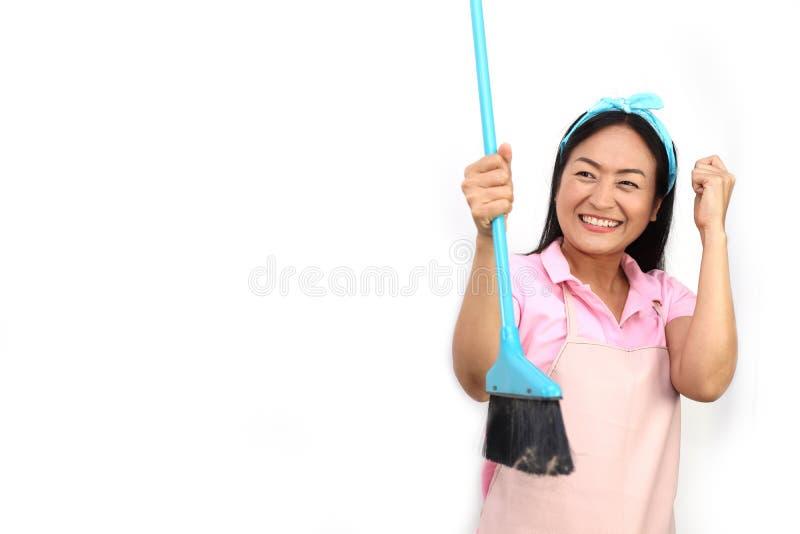 Портрет жизнерадостной азиатской женщины имея потеху пока очищать изолированный на белизне Счастливый веник удерживания домохозяй стоковая фотография