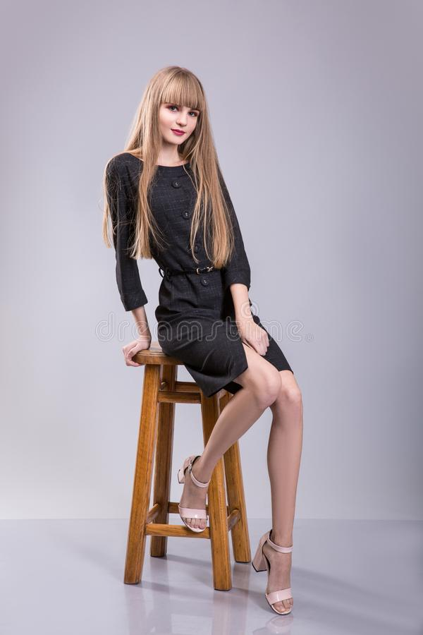 Портрет жизнерадостной женщины в черном платье сидя на стуле и смотря камеру над серой предпосылкой стоковое фото rf