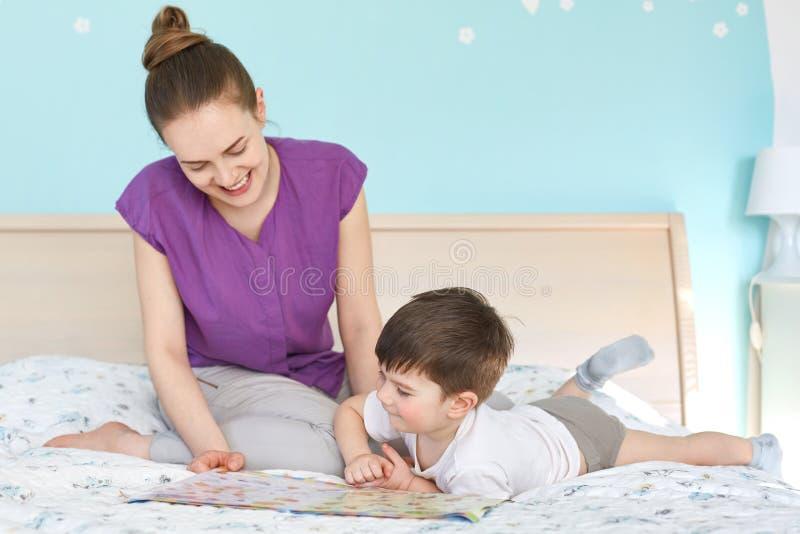 Портрет жизнерадостной симпатичной молодой матери читает сказки для ее сына, сидит совместно на кровати против уютного интерьера  стоковое изображение