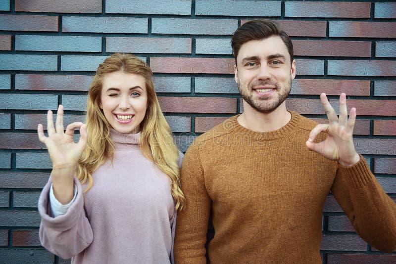 Портрет жизнерадостной усмехаясь пары обнимая и показывая в порядке жест над коричневой кирпичной стеной стоковые фото