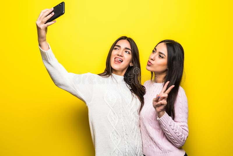 Портрет 2 жизнерадостных девушек одел в свитерах стоя и принимая selfie изолированное над желтой предпосылкой стоковое фото