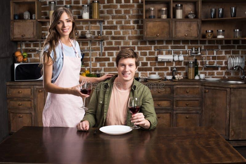 портрет жизнерадостных пар при стекла вина смотря камеру в кухне стоковое фото