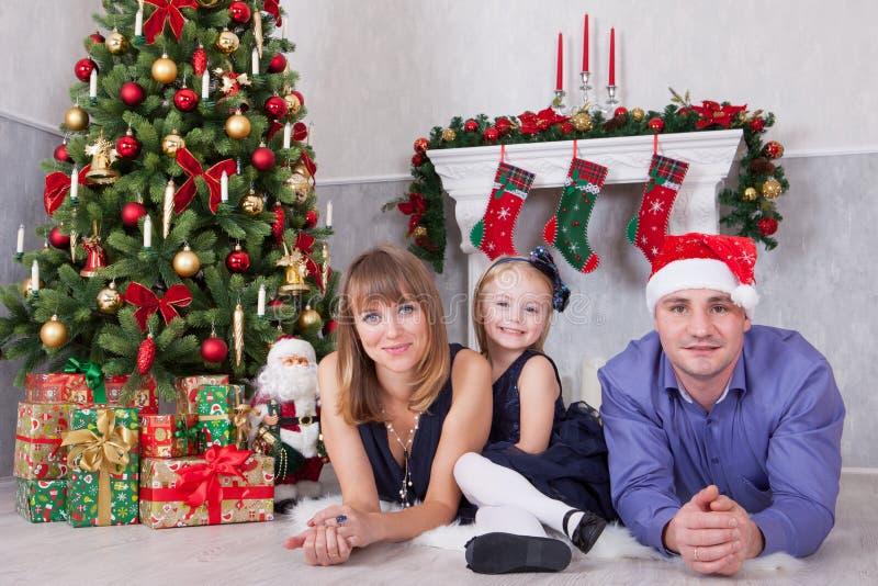 Портрет жизнерадостных счастливых людей семьи из трех человек лежа на поле около рождественской елки с подарками xmas Камин с chr стоковые фото