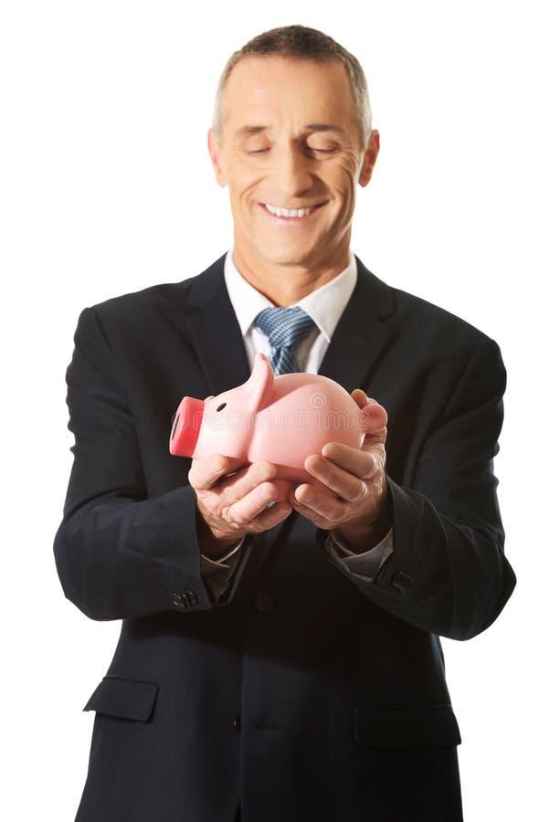 Портрет жизнерадостного бизнесмена держа piggybank стоковое изображение