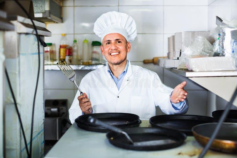 Портрет жизнерадостного зрелого кашевара человека с сковородами на кухне стоковые изображения