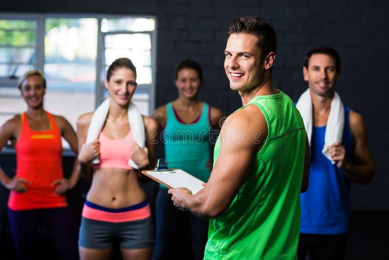 Портрет жизнерадостного инструктора фитнеса с людьми в спортзале стоковые фото