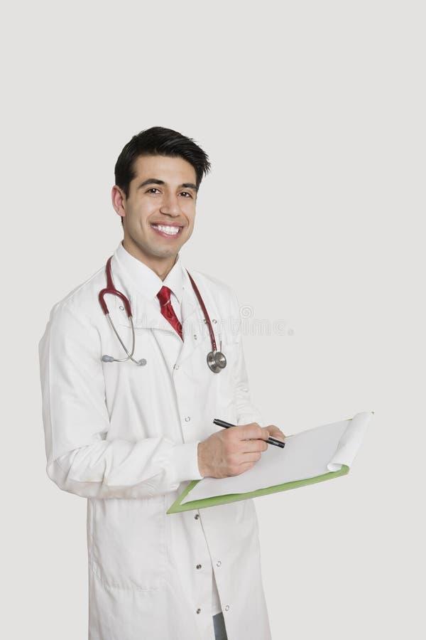 Портрет жизнерадостного индийского мужского доктора держа медицинскую диаграмму над светом - серой предпосылкой стоковые фото