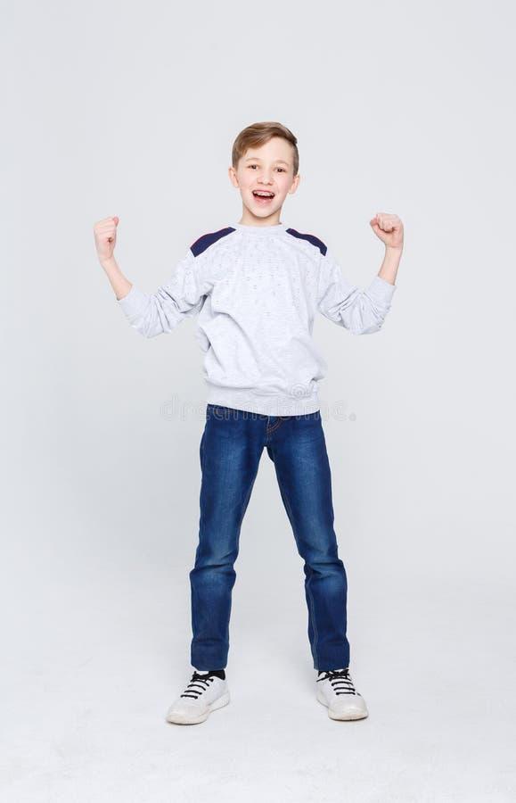 Портрет жизнерадостного мальчика празднуя победу на предпосылке студии стоковая фотография