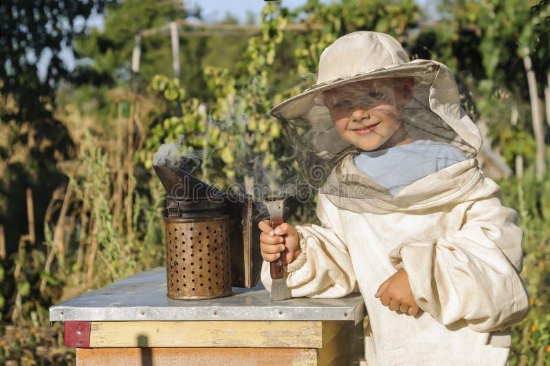 Портрет жизнерадостного beekeeper мальчика стоковое изображение rf