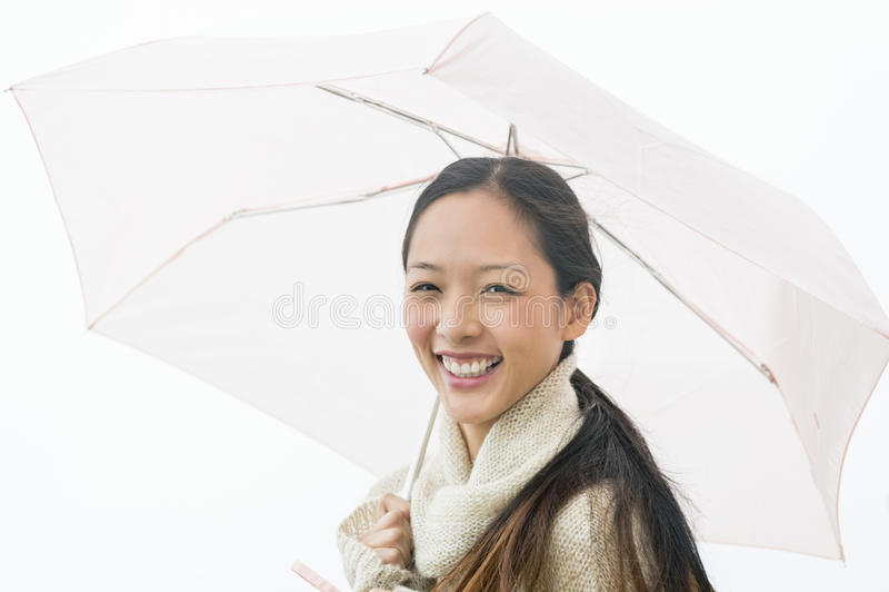 Портрет жизнерадостной азиатской женщины держа зонтик стоковые изображения