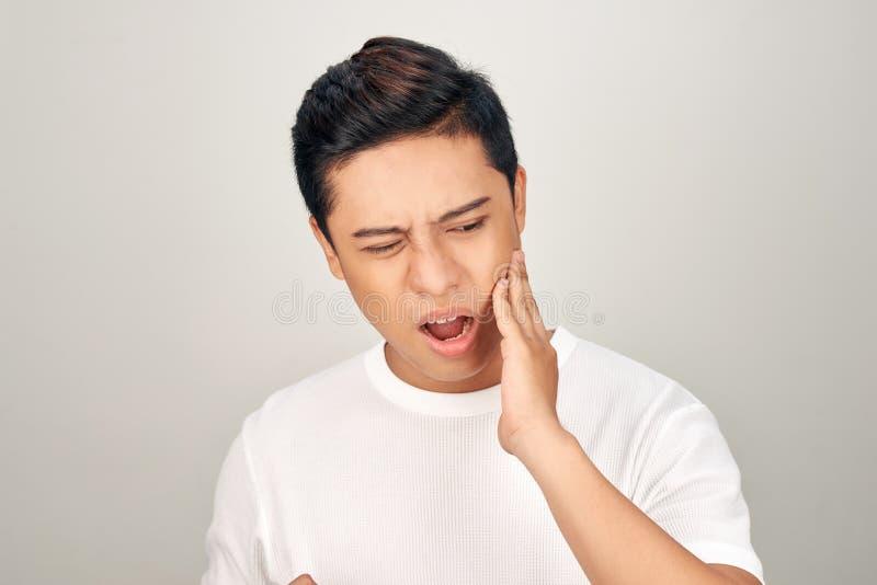 Портрет жирного азиатского человека использовать его руку касается его щеке, чувствуя тягостен от toothache Устная концепция здор стоковое фото