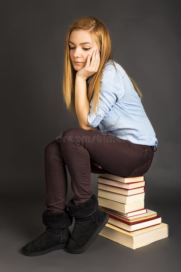 Портрет заботливого девочка-подростка сидя на куче книг стоковое фото