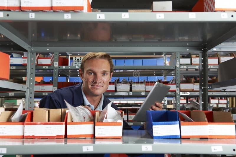 Портрет заводской рабочий используя таблетку цифров в кладовой стоковое изображение