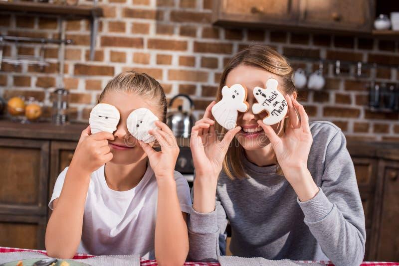 портрет заволакивания матери и дочери наблюдает с печеньями хеллоуина стоковое изображение