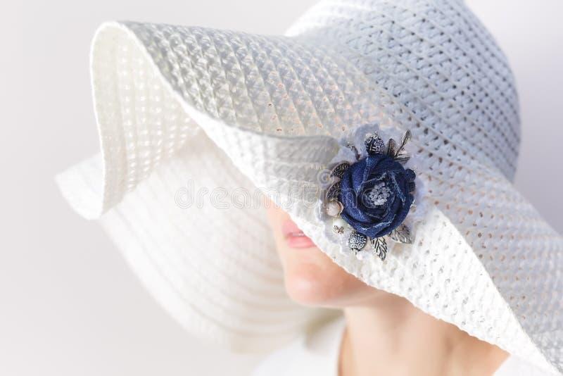 Портрет загадочной женщины в белой шляпе с фибулой сделанной из джинсовой ткани handmade стоковые фотографии rf