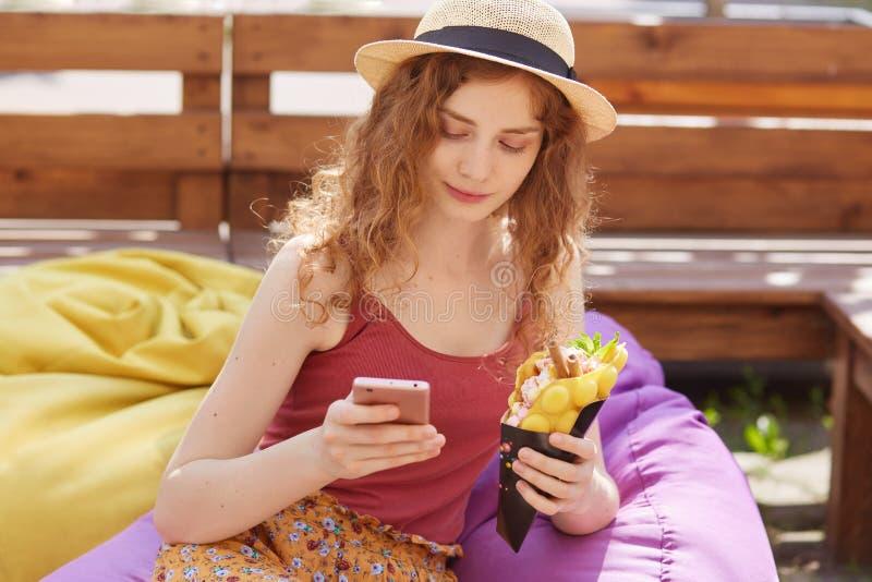 Портрет задумчивой хорошей смотря дамы, имеющ внимательный взгляд, держащ еду и ее смартфон в обеих руках, проверка социальная стоковое изображение