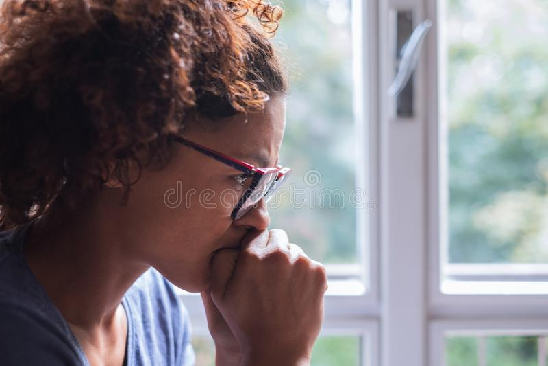 Портрет задумчивой чернокожей женщины стоя около окна стоковая фотография