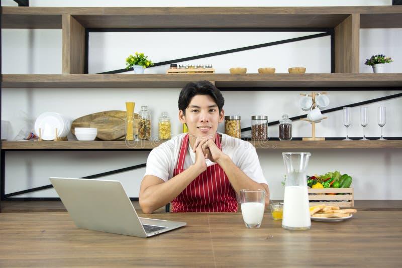 Портрет здорового взрослого человека в красной рисберме усмехаясь и имея кухню завтрака дома стоковое фото