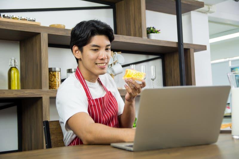Портрет здорового взрослого человека в красной рисберме усмехаясь и имея кухню завтрака дома стоковые изображения