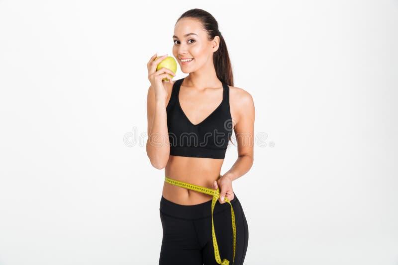 Портрет здоровой азиатской женщины фитнеса держа яблоко стоковое фото