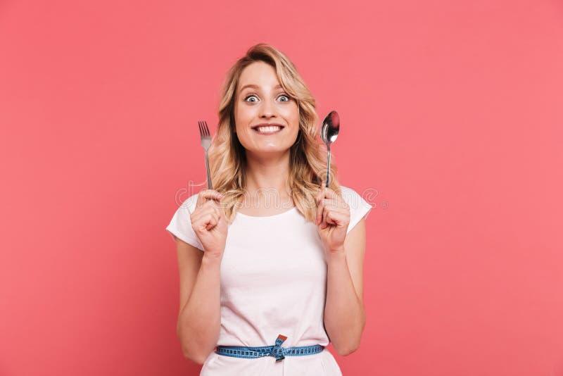 Портрет здоровой белокурой ленты тела женщины 20s нося измеряя вокруг ложки и вилки удерживания талии стоковые фотографии rf