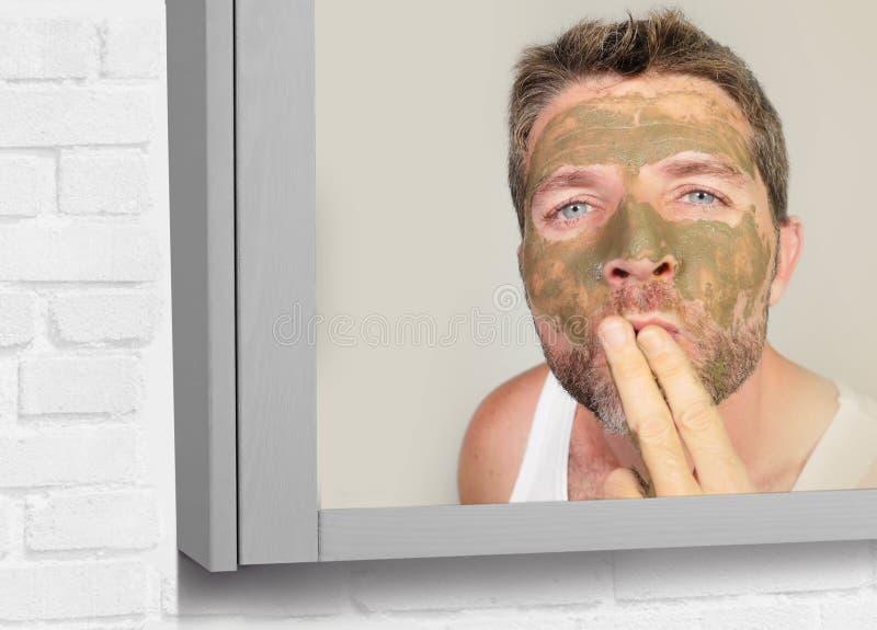 Портрет зеркала ванной комнаты образа жизни молодого привлекательного счастливого человека с зеленой сливк на его стороне приклад стоковые изображения