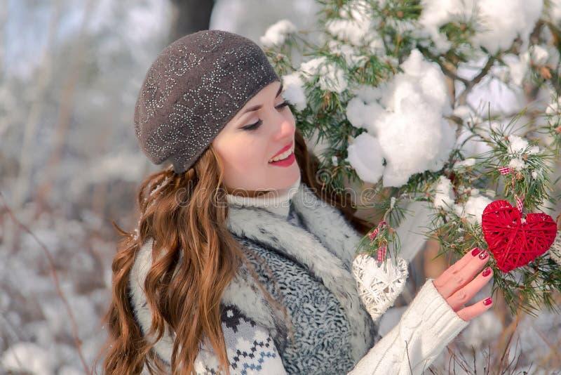 Портрет зимы внешний милой жизнерадостной положительной маленькой девочки с красным украшением сердца на естественной предпосылке стоковые изображения