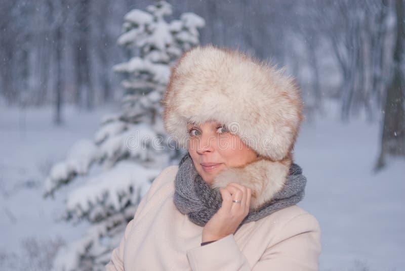 Download Портрет зимы женщины в белом пальто во время снежностей в парке Стоковое Изображение - изображение насчитывающей парк, глаза: 81804113
