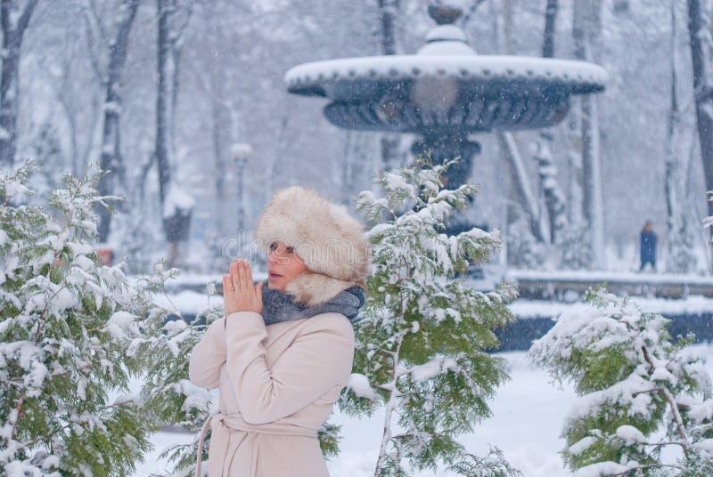 Download Портрет зимы женщины в белом пальто во время снежностей в парке Стоковое Изображение - изображение насчитывающей сосенка, парк: 81804245
