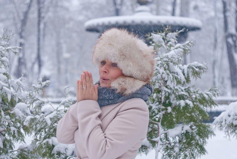 Download Портрет зимы женщины в белом пальто во время снежностей в парке Стоковое Фото - изображение насчитывающей напольно, портрет: 81804274