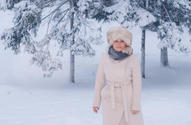Download Портрет зимы женщины в белом пальто во время снежностей в парке Стоковое Изображение - изображение насчитывающей сосенка, лисица: 81804325