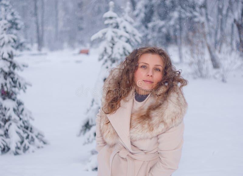 Download Портрет зимы женщины в белом пальто во время снежностей в парке Стоковое Изображение - изображение насчитывающей напольно, бело: 81804573