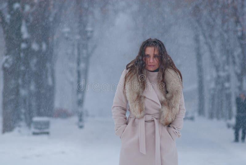 Download Портрет зимы женщины в белом пальто во время снежностей в парке Стоковое Фото - изображение насчитывающей снежности, вал: 81804826