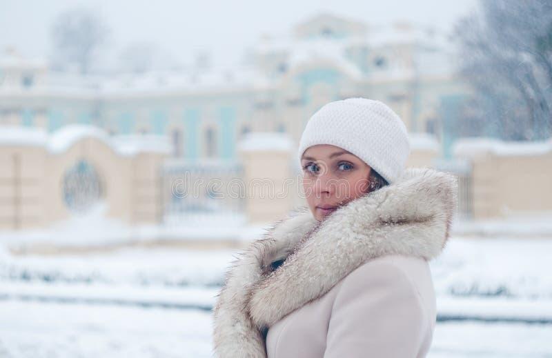 Download Портрет зимы женщины в белом пальто во время снежностей в парке Стоковое Изображение - изображение насчитывающей заморозок, приполюсно: 81804927