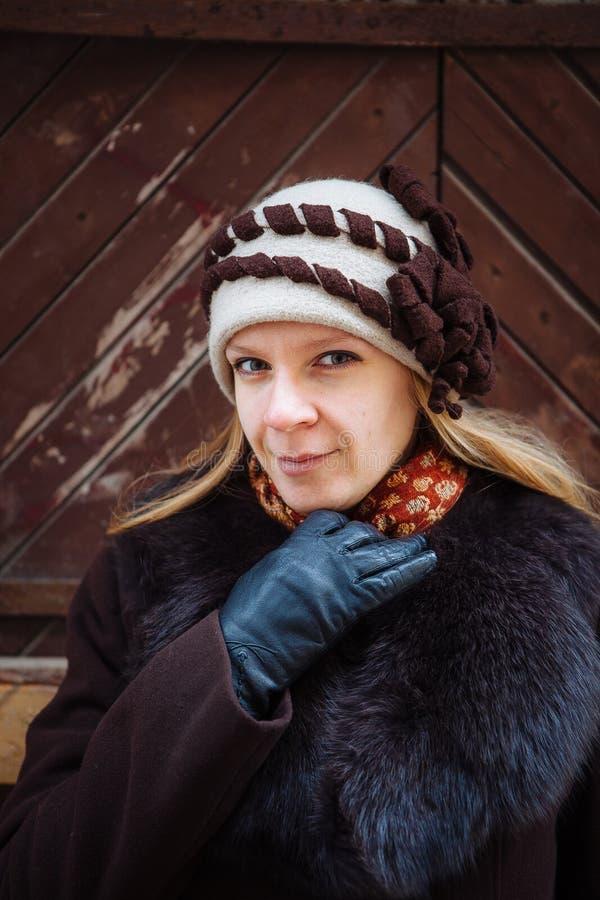 Портрет зимы молодой женщины с шляпой, коричневым пальто и черными кожаными перчатками, внешней стоковая фотография