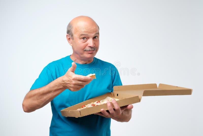 Портрет зрелого европейского человека есть кусок пиццы В его руках он держит коробку еды Всход студии стоковые изображения