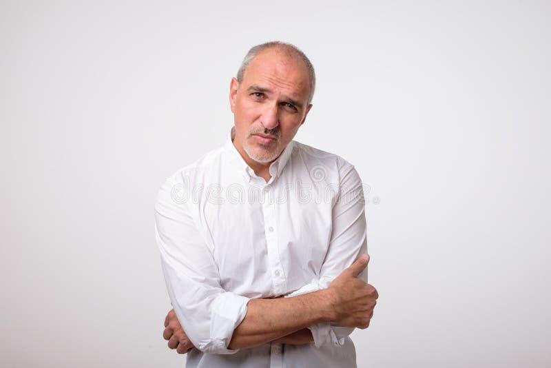 Портрет зрелого красивого человека в белой рубашке с серьезным и унылым выражением на стороне стоковая фотография rf