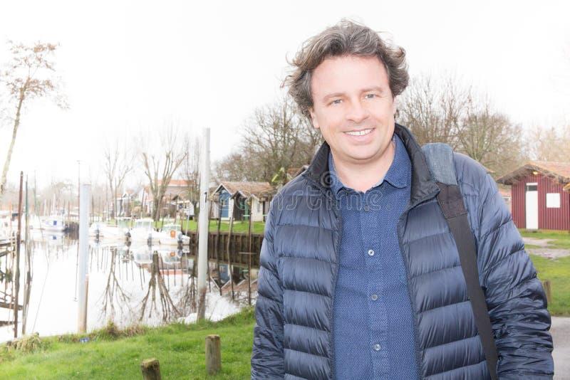 портрет зрелого человека усмехаясь вне близко берега реки озера порта стоковое изображение rf