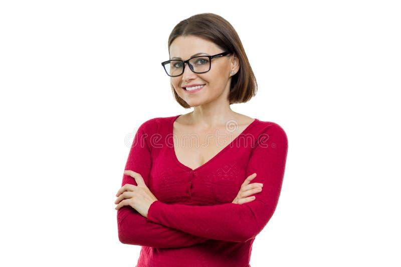Портрет зрелой усмехаясь женщины с стеклами с оружиями пересек, белая изолированная предпосылка стоковые изображения rf