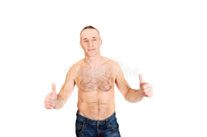 Портрет зрелого без рубашки человека с одобренным знаком стоковые изображения