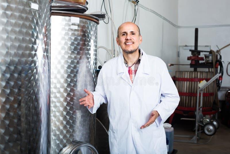 Портрет зрелого мужского работника винодельни стоя на фабрике i вина стоковое фото rf