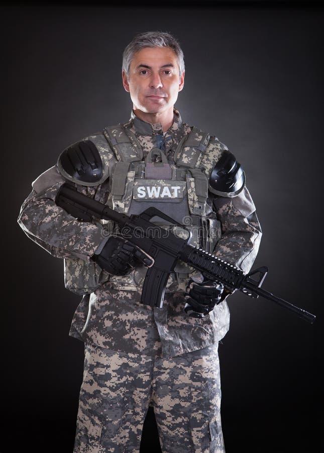 Портрет зрелого солдата держа оружие стоковая фотография